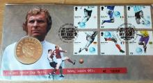 Lot 486 - First Day Cover showing Bobby Moore as well as 6 stamps and a coin - Robert Frederick Chelsea Moore OBE (12 April 1941 – 24 February 1993) was an English professional footballer. He captained West Ham United for more than ten years and was captain of the England team that won the 1966 World Cup. He is widely regarded as one of the greatest defenders of all time, and was cited by Pelé as the greatest defender that he had ever played against.[3] Moore is a member of the World Team of the 20th Century.