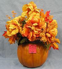 Pumpkin shaped vase with autumn flower arrangement
