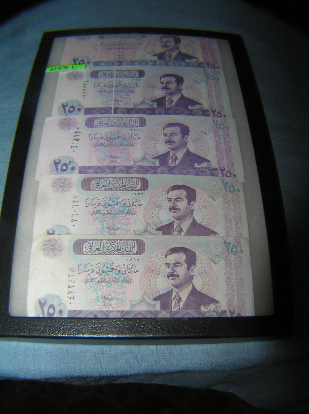 Group of Iraqui currency featuring Saddam Hussien