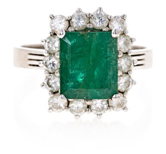 A ring with a central emerald and diamondsWhite gold, emerald cut emerald, 2.73 cts and brilliant cut diamonds, 0,77 cts. Small breakag