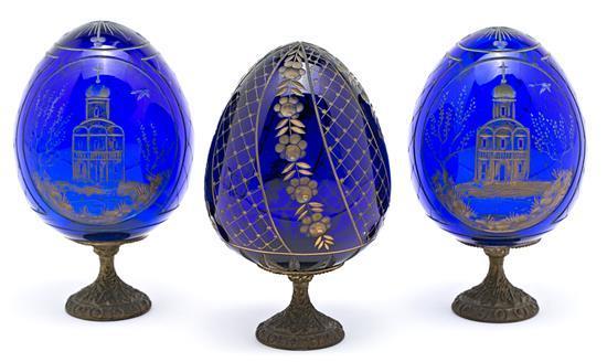 Juego de tres pisapapeles rusos en forma de huevo en vidrio azul grabado y dorado y pie en bronce, de la primera mitad del siglo XX