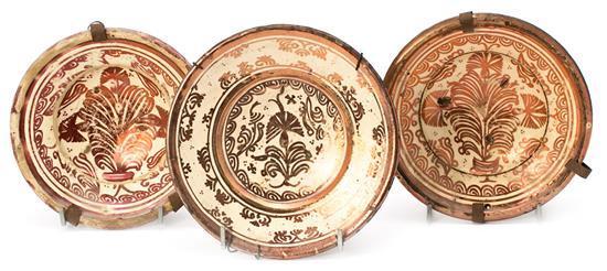 Tres platos en loza de reflejo metálico de Manises, del siglo XVIII