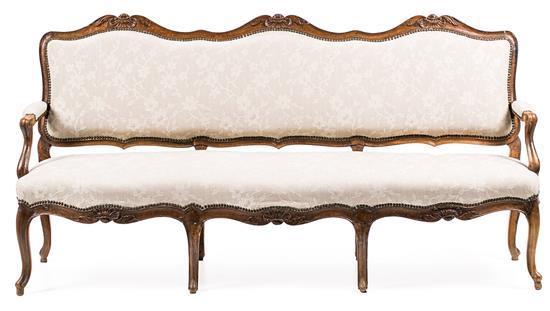 Juego de sofá, pareja de sillones y seis sillas Carlos III en nogal tallado, del tercer cuarto del siglo XVIII
