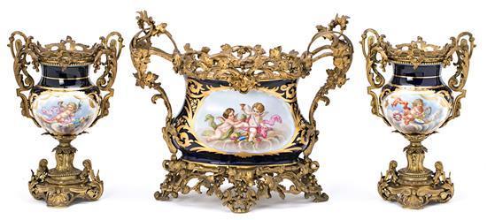 Guarnición francesa formada por centro y pareja de jarrones en porcelana