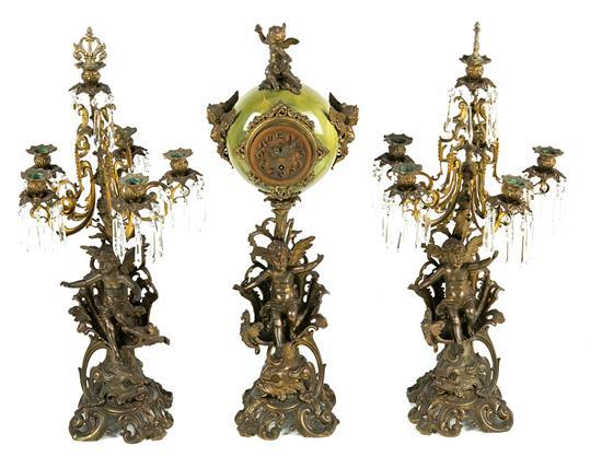 Guarnición francesa Art Nouveau formada por reloj y pareja de candelabros en calamina dorada y loza simulando ónix, de finales del s...