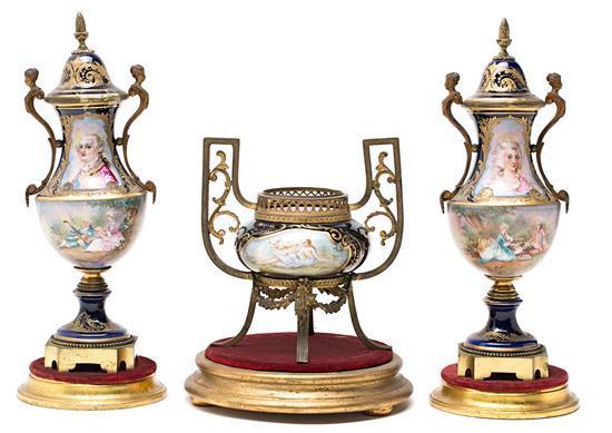 Guarnición francesa formada por pareja de jarrones y centro en porcelana tipo Sèvres con monturas en metal dorado, de principios del...