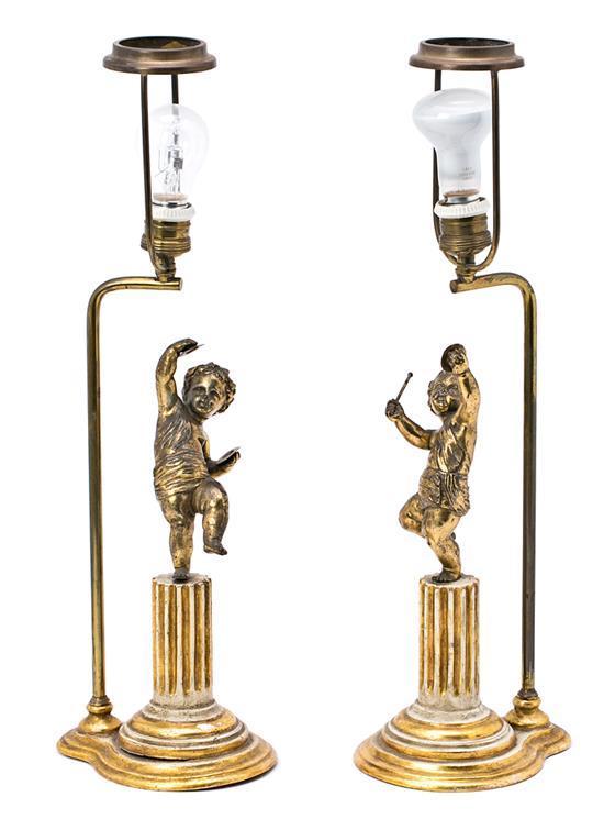 Pareja de lámparas de sobremesa con pie en madera tallada y policromada, rematadas por las figuras de dos niños en bronce, del prime...