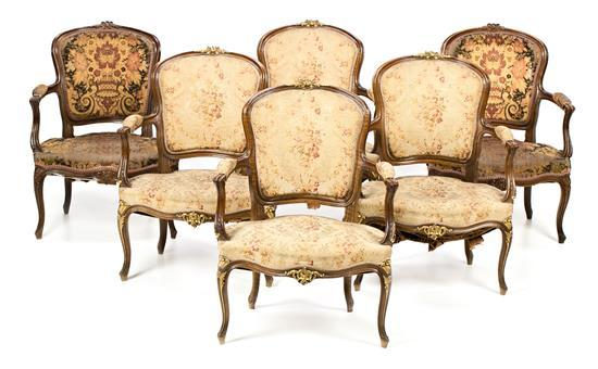Juego de seis sillones y espejo estilo Luis XV en nogal tallado, de las primeras décadas del siglo XX