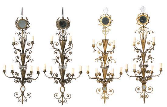 Juego de cuatro apliques estilo Pierre Lottier en hierro forjado y metal dorado, de mediados del siglo XX