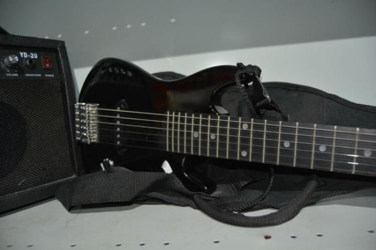 Child's black electric guitar and amplifier in