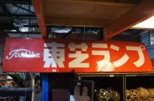 Large vintage Japanese enamel on metal advertising sign for Toshiba, white characters in English & Japanese on red ground, 45 x 180cm