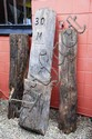 3 various carved timber roadside mile markers