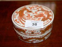 Small Chinese circular porcelain box with iron red and gilt decoration with dragon and phoenix, character marks to underside, 10cm D