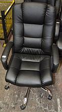 A black executive office arm chair on a chrome 5