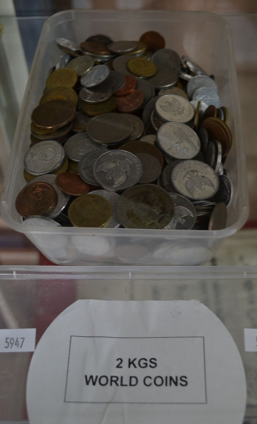 Plastic tub with assorted coins of the world