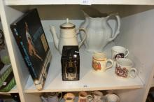 Shelf: vintage box camera, Bruce Springstein boxed set of 3 cassettes 1975-85, large white jug, 3 x Royal theme coffee mugs