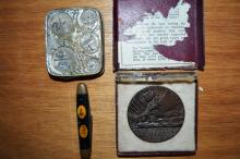 3 items: a replica 'Sinking of the Lusitania' medallion, an antique coin holder and an old Polding pocket knife, inset with images of king & queen