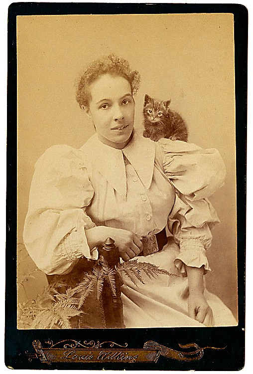 A woman has a kitty on her shoulder.