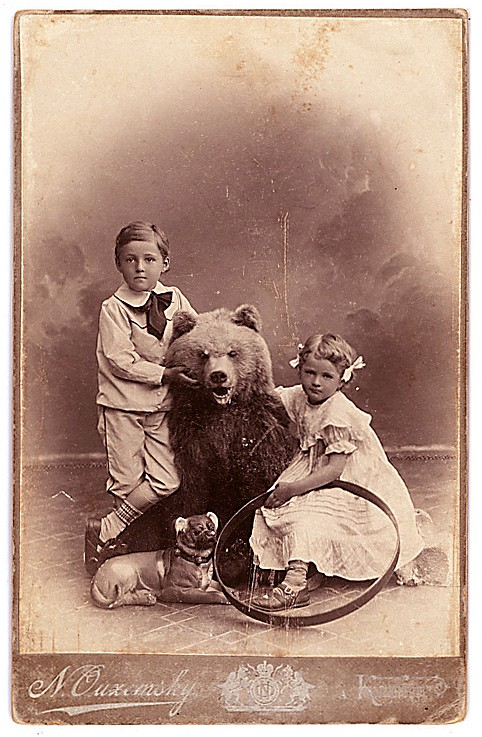 Ukrainian children with a stuffed bear, dog and hoop.