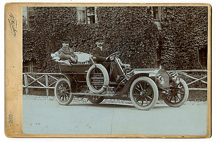 An early open automobile with a chauffeur