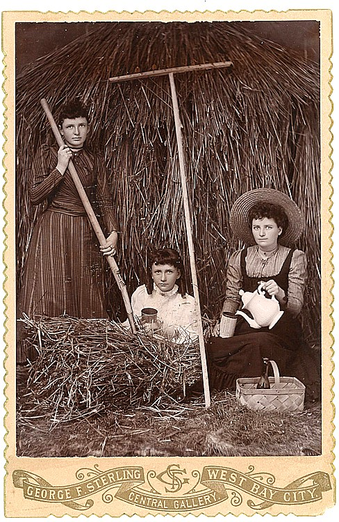 Women and a girl take a break from haying.
