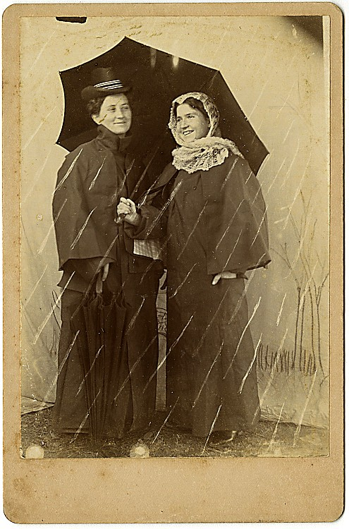 Two smiling women in the rain.