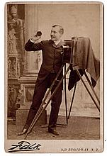 A jaunty photographer with his camera holds the lens cap