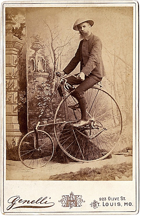 A man in riding position on his high wheel bicycle.
