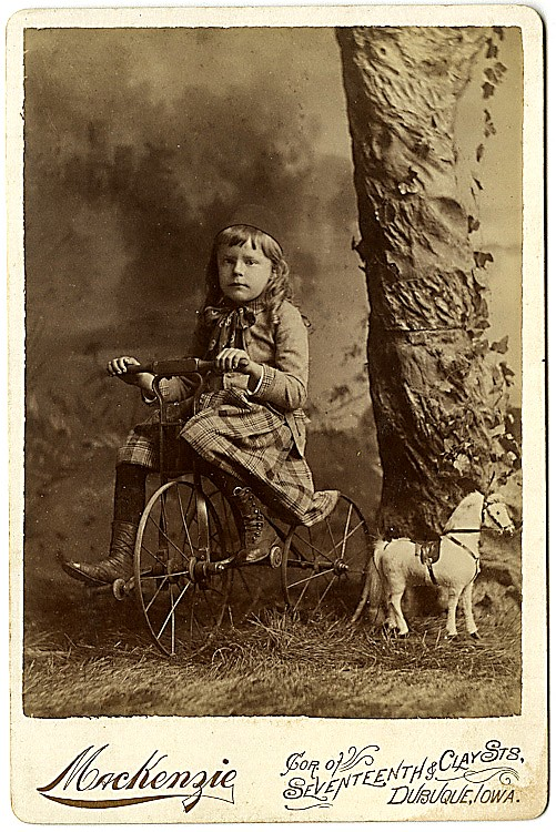 A girl on a tricycle with a toy stuffed horse.