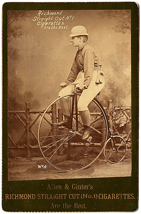 A woman on a high wheel bicycle.