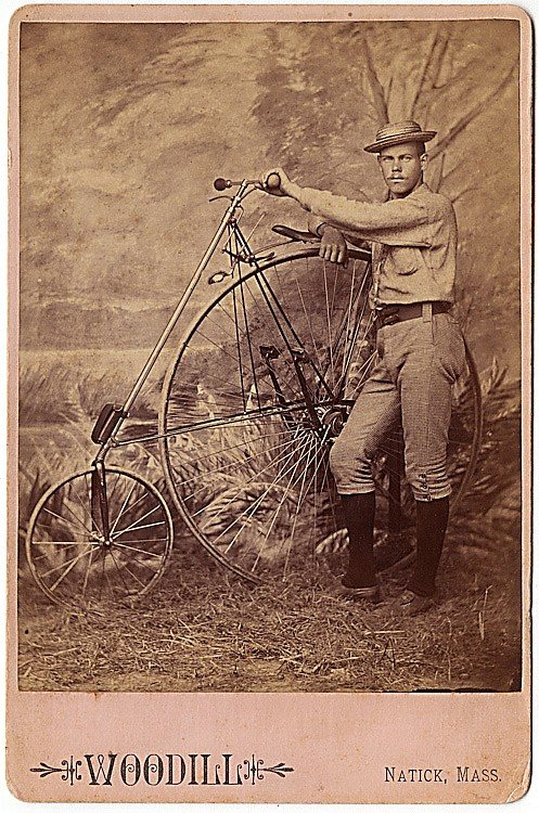 A man with his high wheel bicycle.