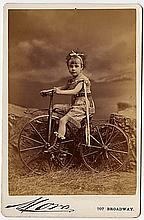 Ettie Brown, the child actress in costume on a bicycle, by Mora.