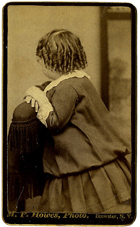 A curly-haired girl is seen from the back