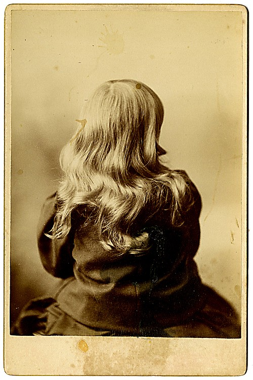 A long-haired girl is seen from the back.