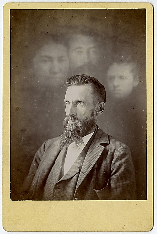 A spirit photograph. A gentleman is concentrating, visited by the spirits of his parents and wife.