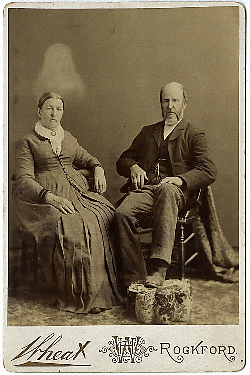 A spirit photograph. An elderly couple, sitting separately, is visited by an apparition, probably a deceased daughter.