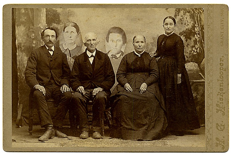 An elderly family with portraits of deceased members added.