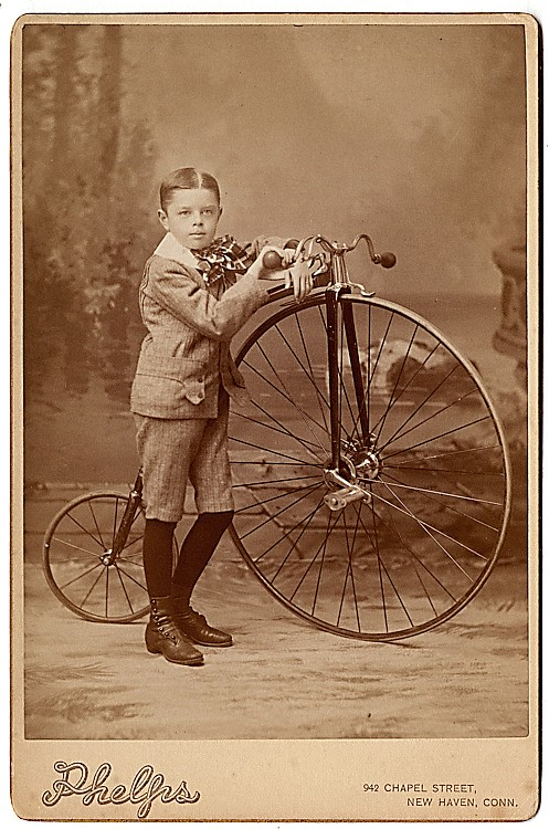 A boy with his high-wheel bicycle