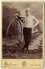 A rider stands beside his high wheel bicycle, in his riding clothes.