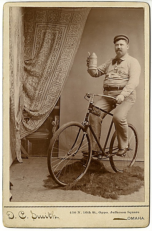 A bicycle rider with a stein of beer.