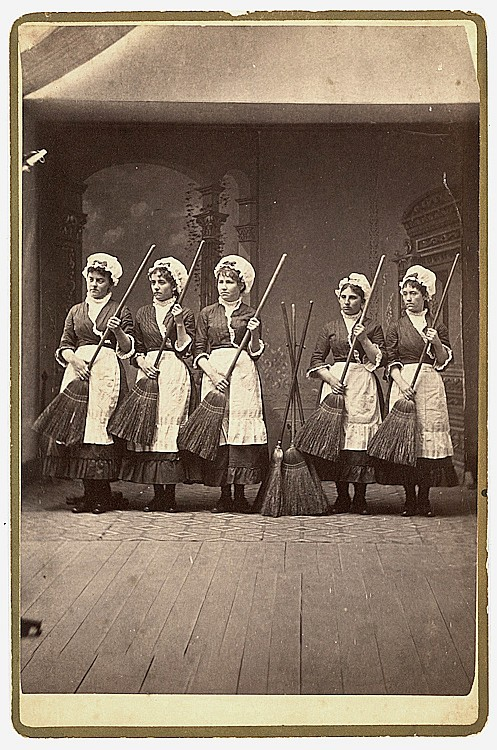 Cleaning staff. This is a rhythmic line-up of 5 maids with their brooms.
