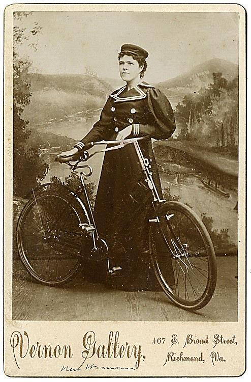 A woman in her riding outfit, with her bicycle.