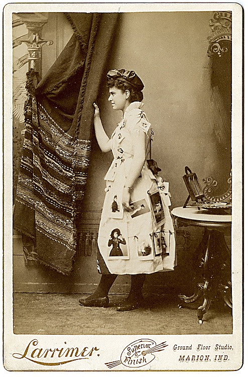 A photo advertising lady, posed in profile, with cabinet cards attached to her dress. .