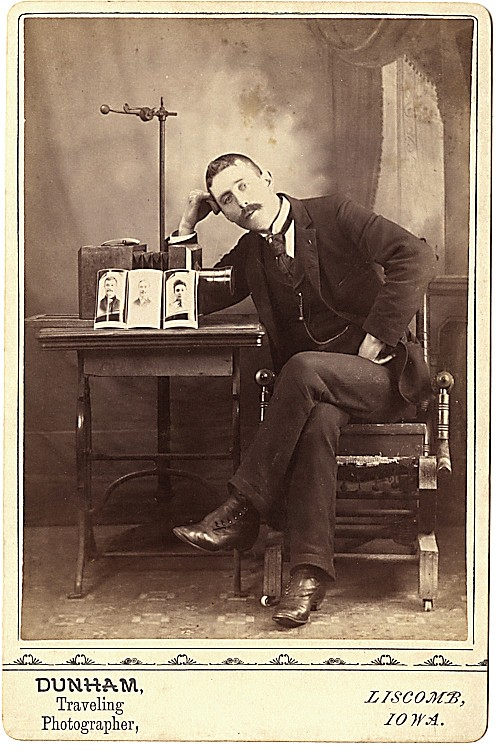 A photographer with a camera and cabinet cards on a table, with a posing stand behind.
