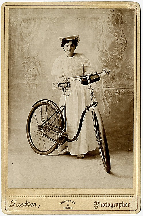"A woman with her bicycle. ""Ivoryette Finish"" cabinet card by Tasker"