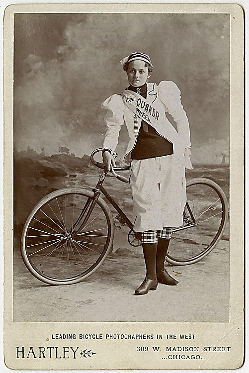 "A woman bicyclist in her riding clothes, with a sash reading ""The Quaker Wheel."""