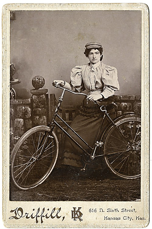A woman bicyclist with a cap, a full blouse, a long skirt, with her bicycle.