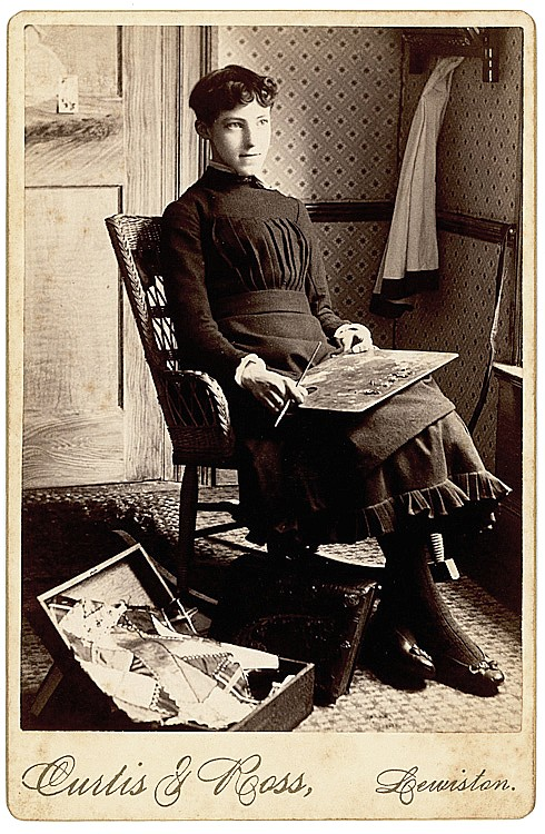 A woman painter with an easel on her lap, scraps of material on the box on the floor.