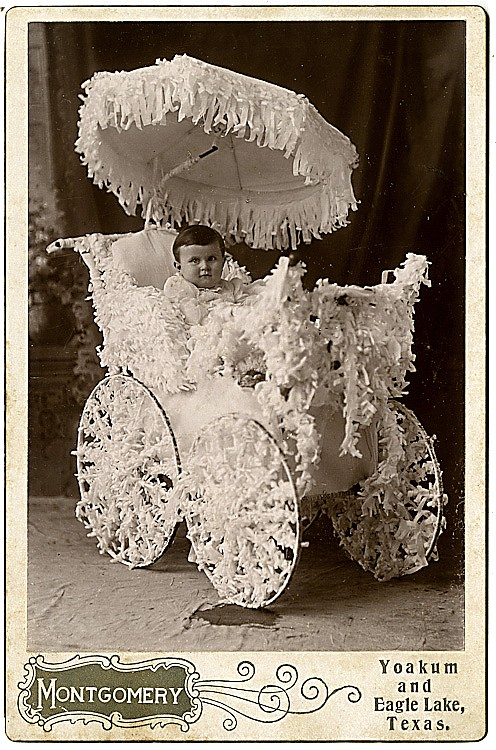 A baby Texan in a carriage festooned with ribbons.