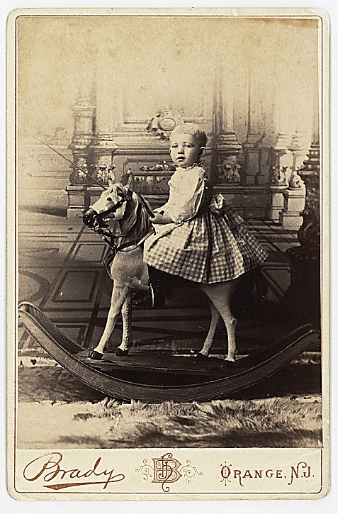 A baby on a rocking horse, by Brady, Orange, New Jersey.